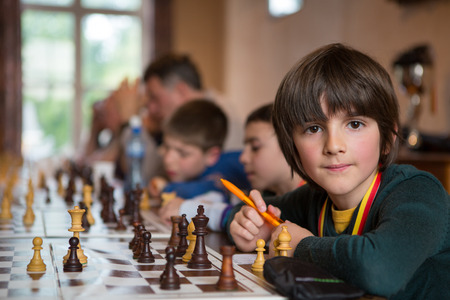 BRUSSELS, BELGIUM, JUNE 26: Serious little boy playing chess holding a pen and looking at the camera while other students are learning chess in the background with a teacher. Brussels 2013