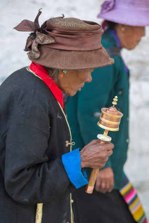 decreased: CHINA, TIBET, APRIL 18: Unidentified old woman praying with prayer roll at the Palkhor Monastery in Lhasa. Since 2008, the number of Tibetan people has decreased down to two millions people. Tibet 2013.