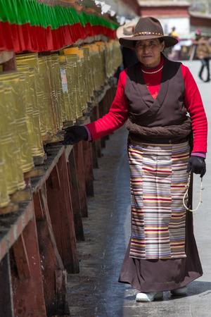LHASA, TIBET, APRIL 16: Old unidentified Tibetan woman praying along the pilgrim circles the Potala palace in Lhasa. Devotees walk every day around the Holy palace, April 16, 2013, China