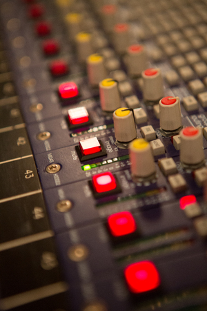 Audio mixer mixing board fader and knobs at night during a live concert photo