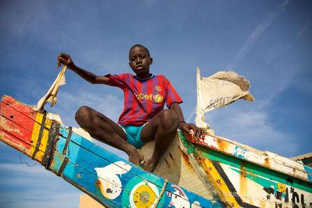 unicef: SAINT-LOUIS, SENEGAL, 4 dicembre: non identificato ha fatto si siede su una colorata barca di pescatori con t-shirt UNICEF e un cielo blu sullo sfondo. Saint Louis, Senegal 2010. Editoriali