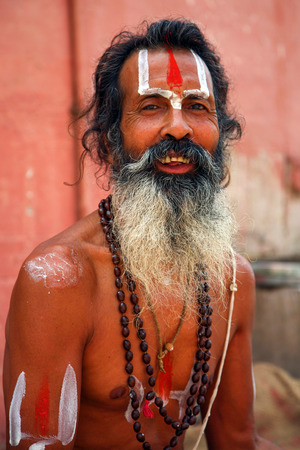 INDIA, VARANASI, JUNE 1: Portrait of an Holy Sadhu man with traditional painted face, praying near by the Gange in Varanasi, India. In Hinduism, sadhu is a common term for a mystic, an ascetic, practitioner of yoga and wandering monks, June 1, 2009, India
