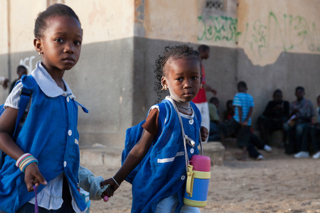 SAINT-LOUIS, SENEGAL, NOVEMBER 8  Unidentified very young African sisters dressed in blue on the way to school with other students in the background
