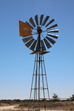 somewhere: Detail of a bore water wind mill in action with a blue sky somewhere in south africa
