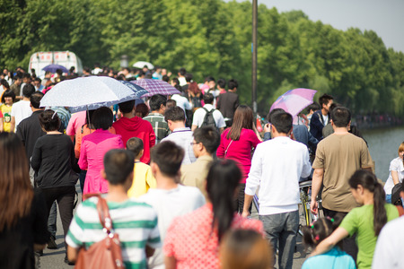 HANGZHOU, CHINA, MAY 1: Crowd walking along the lake in Hangzhou on the 1st of May, the Labour Day in China, 2013.