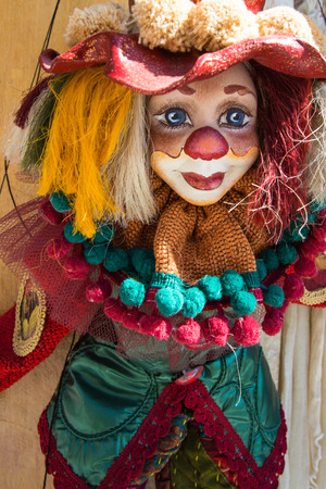Puppet on a string, colorful clown dressed with clothes in the streets of Santorini, Greece 2013.