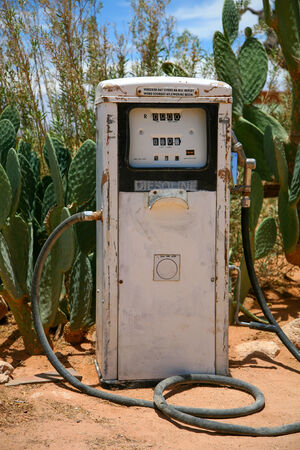 Old and rusty gaz station surrounded by cactus before the Namibian desert in a city called Solitude. Stock Photo