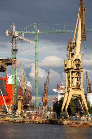 shiprepair: Gdansk, north of Poland on the Baltic Sea, huge red ships in a dry dock with massive cranes around, Gdansk. Poland 2013. Editorial