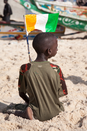 SAINT LOUIS, SENEGAL, DECEMBER 17: Unidentified Kid playing on the beach and holding a senegalese flag. Saint Louis, Senegal, December 17, 2013 Editorial