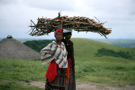 COFFEE BAY, SOUTH AFRICA, JANUARY 13: Two unidentified African women resting while carrying wood for the fire with the nature and a hut in the background. Garden Road, South Africa 2007