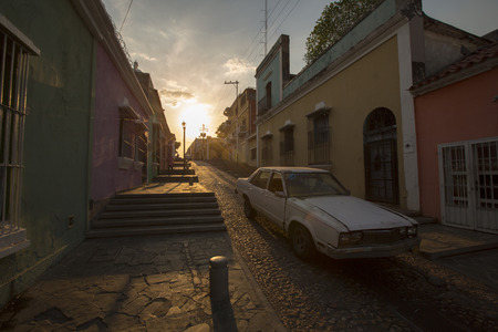 latina america: CIUDAD BOLIVAR, VENEZUELA, APRIL 9: Sunset in old colonial street with a car going through, very typical view of Ciudad Bolivar with its old street stairs in Venezuela. April 9, 2015. Editorial