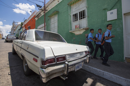 latina america: CIUDAD BOLIVAR, VENEZUELA, APRIL 9: Old wreck car parked in the old colonial city of Ciudad Bolivar with kids walking back from the school dressed in their blue uniform. Venezuela. April 9, 2015.