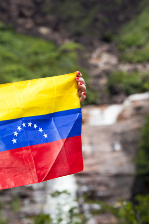 venezuelan: The Venezuelan flag in the woman hands with the Angel Fall in the background, Venezuela 2015.