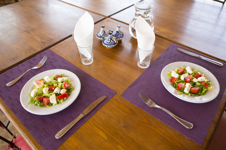 moroccan culture: Close up of a tasty Moroccan green salads plates with goat cheese and fresh tomatoes served on the table in Essaouira restaurant.