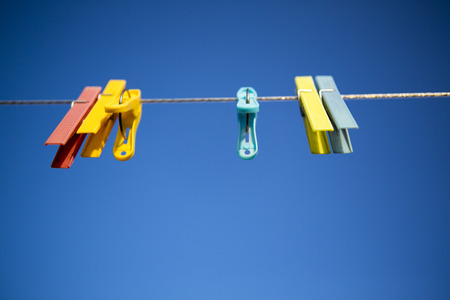 Clothes line with colored clothespins against a blue sky background Stock Photo