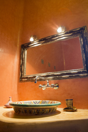 toilet sink: Moroccan themed spa and bathroom in Morocco. View of the sink and the mirror with lighting equipment above.