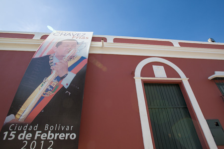 colonial building: CIUDAD BOLIVAR, VENEZUELA, APRIL 9: Poster of Hugo Chavez President of Venezuela celebrating the 15th of February hanging on the facade of an old red colonial building against a blue sky in Ciudad Bolivar, Venezuela 2015.