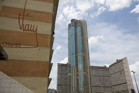 caracas: CARACAS, VENEZUELA, APRIL 20: Downtown of Caracas with view on hight residential buildings, the official signature of President Hugo Chávez is also visible on a wall in the foreground. Venezuela 2015 Editorial