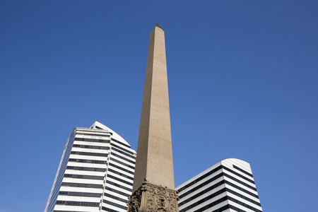 caracas: Plaza Francia in Altamira disctrict in Caracas. Obelisk in between two modern white buildings against a blue sky. Venezuela 2015