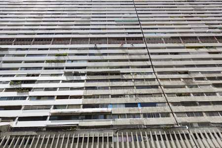 caracas: Old massive residential building in downtown with painters at work hanging with ropes in Caracas center. Venezuela 2015.