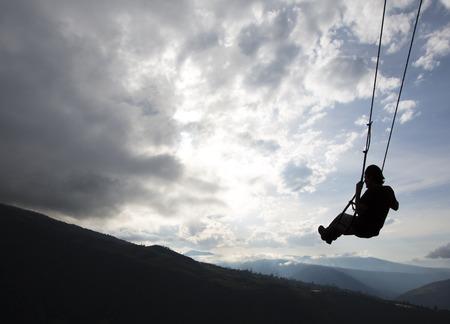 arbol: Silueta de hombre joven feliz en un columpio con una fant�stica vista de la monta�a en la Casa del Arbol, Ecuador