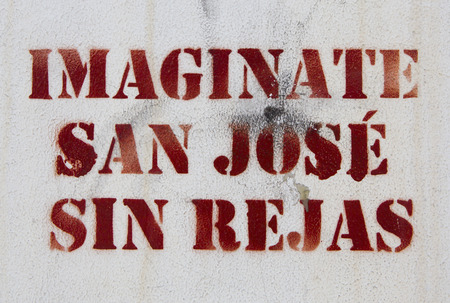 expressing artistic vision: Words Imagine San Jose without gates graffiti on a white wall in the street of Costa Rica