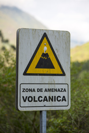 advisement: Wooden arrow sign preventing that the zone is a volcanic area. banos, Ecuador 2015
