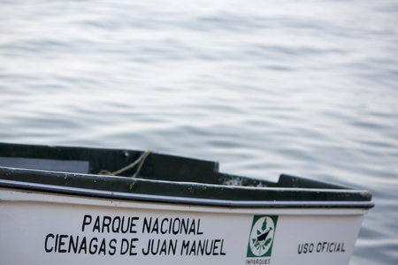 infrastructures: MARACAIBO, VENEZUELA, APRIL 28: Close up of small white wooden boat with the official logo and the name of National Park Cienagas de Juan Manuel with water in the background. Venezuela 2015.