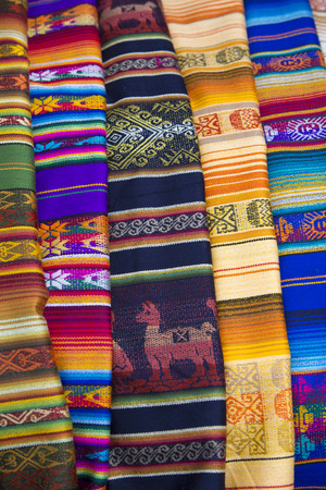 artisanry: Closeup image of classical colorful Peruvian and Bolvian clothes and handicraft at the indigenous market in Otavalo. Ecuador 2015.
