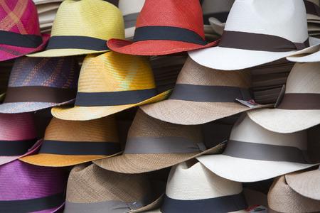 sombrero: Grupo de los sombreros de colores para la venta, que cuelgan en una pared, el mercado de Otavalo. Ecuador Foto de archivo