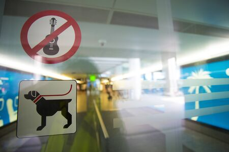 dog allowed: No guitar and free dog allowed sign stickers on transparent doors at the entrance of a international airport