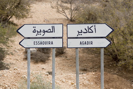 mid distance: Which direction you want to take in Morocco... Road sign in Morocco with bush in the background. Road to Agadair or Essaouira