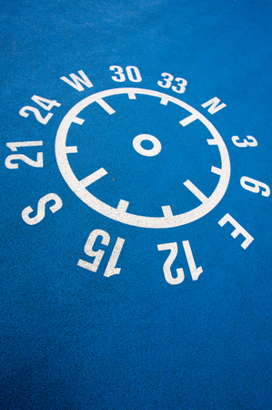 coordinates: White shape of compass printed with coordinates and numbers on a blue clean concrete floor. Stock Photo