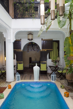 moroccan culture: Interior view of an Arabian Riad interior with swimming pool and traditional furnitures, carpets, Marrakech, Morocco, North Africa.