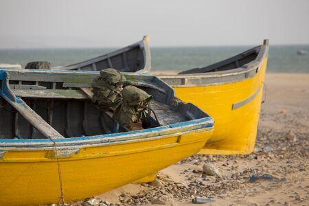 yellow boats: Two yellow and blue fishing boats standing on the beach of Sidi Kaouki near Essaouira in Morocco Stock Photo