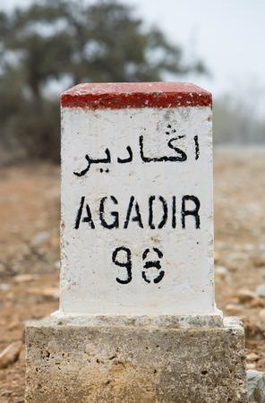 kilometres: Agadir 98 kilometres - road sign distance indicator on the road to Agadir with blurred background, Morocco