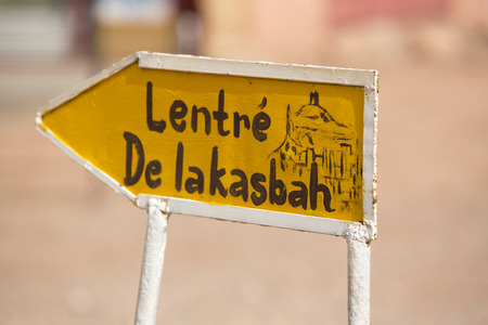 store sign: Old yellow Open sign to the fortified city in Ait-ben-Haddou, a fortified city, or ksar, along the former caravan route between the Sahara and Marrakech in present-day Morocco. Ait Benhaddou has been a UNESCO World Heritage Site since 1987 Stock Photo