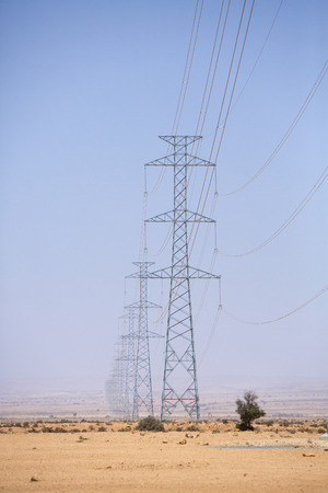 hottest: Electrical towers across a desert background and blue sky near Tata, in the hottest region of Morocco in 2014. Stock Photo