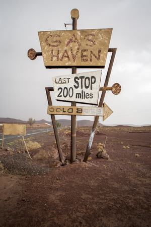 old sign: Tall vintage and abandoned gas sign standing along the deserted road to Ouarzazatein in Morocco. Stock Photo