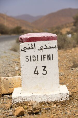 kilometre: Sidi Ifini 43 kilometres - road sign distance indicator on the road to Sidi Ifini with blurred background, Morocco