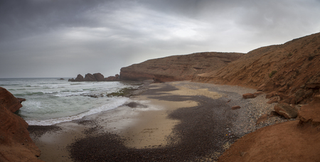 life threatening: Empty and wild beach with cliffs on Legzira coast in the south of Morocco Stock Photo