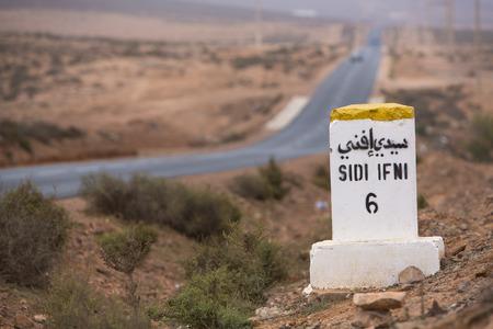 kilometres: Sidi Ifini 6 kilometres - road sign distance indicator on the road to Sidi Ifini with the road in the background, Morocco Stock Photo