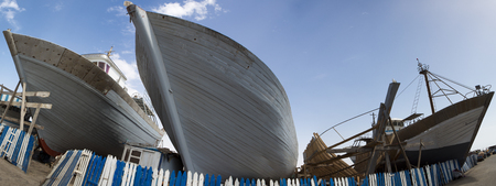 shipbuilder: Panorama of wooden fishing boats under construction in shipyard in the harbour of Essaouira against a blue clear sky, Morocco. Editorial