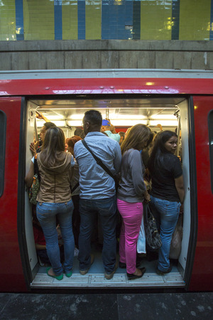 insufficient: CARACAS, VENEZUELA, APRIL 20: People standing during the rush hour in a subway train wagon with open doors in Caracas. In 2015, the transit system seems totally insufficient for a capital city.