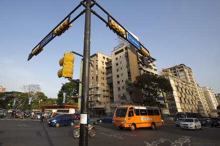 Caracas, Venezuela, 20 april: Straat kruising met kleine verkeer, bus, auto's en moto's, vroeg in de ochtend in Caracas tegen een blauwe hemel, Venezuela 2015. Redactioneel