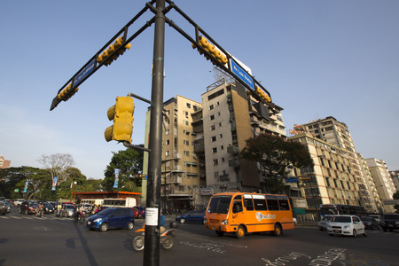 caracas: CARACAS, VENEZUELA, APRIL 20: Street crossing with small traffic, bus, cars and motos, early in the morning in Caracas against a blue sky, Venezuela 2015. Editorial