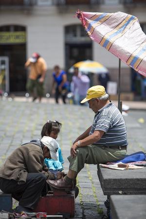 humiliation: QUITO, ECUADOR, FEBRUARY 23: shoeshiner at work in the historic center of Quito. Historic center of Quito is the first UNESCO World Heritage site. Quito, Ecuador 2015.