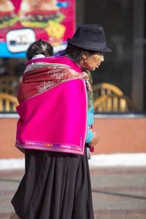 indian artifacts: OTAVALO, ECUADOR - FEB 28, 2015: Unidentified Ecuadorian old woman and her daughter at the Otavalo Market. Most of the Ecuadorian people belong to the Mestizo ethnic group, famous for their art and music. Ecuador 2015.