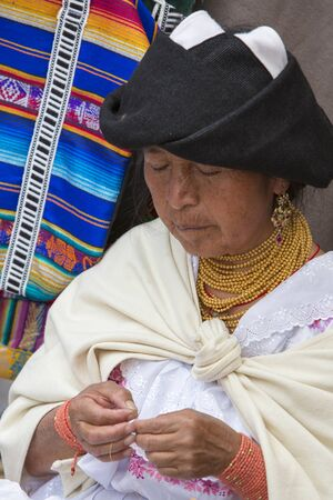 indian artifacts: OTAVALO, ECUADOR - FEB 28, 2015: Unidentified Ecuadorian old woman at work at the Otavalo Market. Most of the Ecuadorian people belong to the Mestizo ethnic group, famous for their art and music. Ecuador 2015.