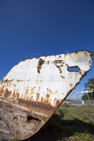 water stained: An old boat against a clear blue sky, weathered by the elements, is pulled up on the beach in the harbor of Puerto Villamil. Galapagos Islands, Ecuador 2015